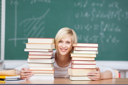 Portrait of happy female student with stacked books at desk in classroom photo