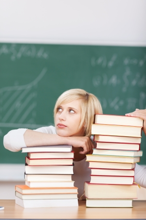 tired female student leaning on stacked books in classroom photo