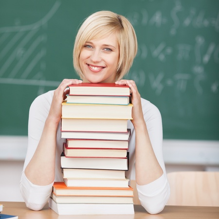 young smiling woman in classroom with head on stacked books photo