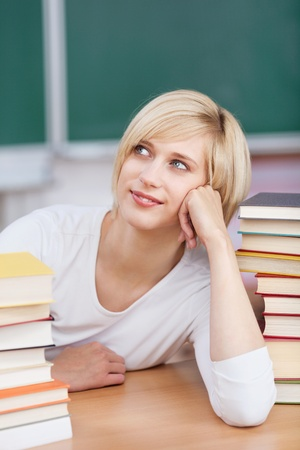 thoughtful student between books leaning her head on photo