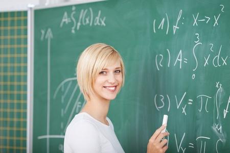 sumas: Retrato de joven estudiante resolver sumas en la pizarra en el aula
