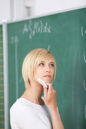 sums: Thoughtful young female student with hand on chin solving sums on chalkboard in classroom