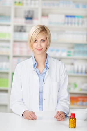Portrait of young female pharmacist with pill bottle and prescription paper standing at pharmacy counter Stock Photo - 21112233