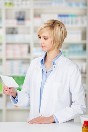 female pharmacist looking at prescription at the counter photo