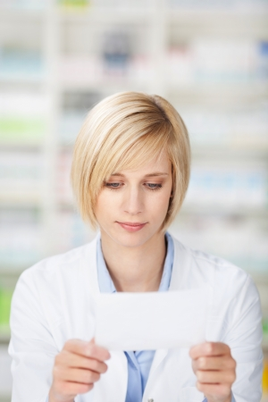 female pharmacist reading on a paper with copyspace photo