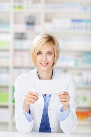 Portrait of young female pharmacist holding prescription paper while leaning on pharmacy counter photo