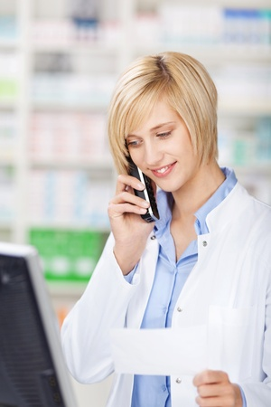 Young female pharmacist holding prescription paper while using cordless phone in pharmacy photo