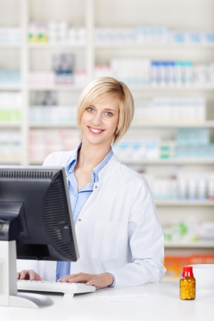 Portrait of young female pharmacist using computer at pharmacy counter photo