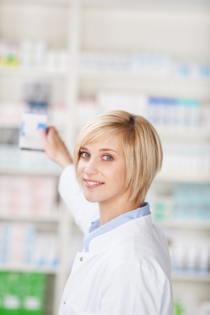 Portrait of young female pharmacist taking out medicine from shelf in pharmacy photo