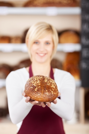 smiling saleswoman in bakery showing bread in her hands photo