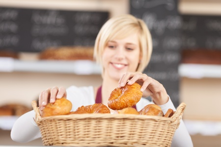 pastry shop: Young waitress arranging breads in basket at cafe