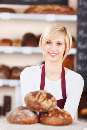 portrait of a smiling salesgirl working in bakery photo
