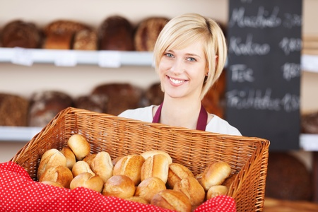 Portrait of young waitress with bread basket in cafe photo