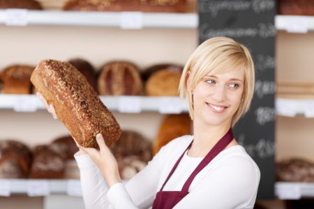 salesgirl: smiling salesgirl holding a bread in bakery