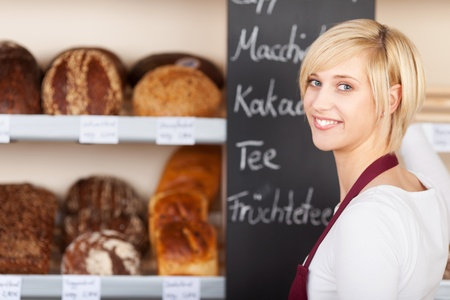 saleswoman in bakery writing offers on blackboard photo