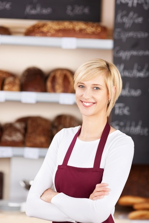 Portrait of confident waitress with arms crossed standing in bakery photo