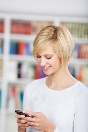 Happy young woman messaging on mobile phone in library photo