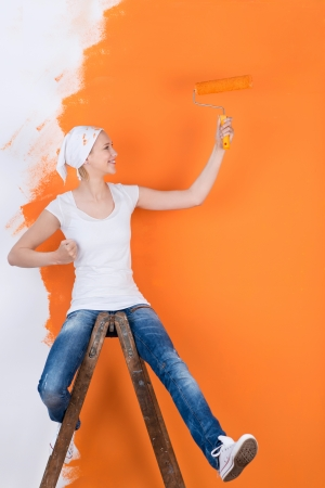 woman sitting on ladder and having fun while painting wall photo