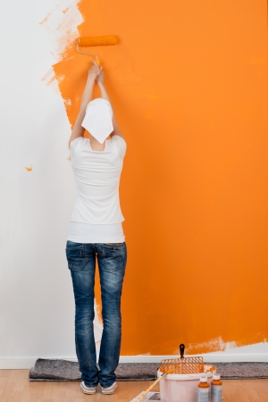 Full length rear view of young woman painting wall with roller in house photo