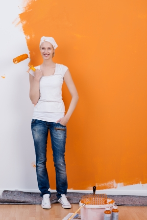 smiling woman painting her apartment with orange color photo