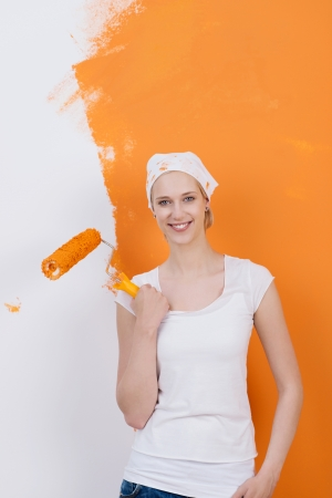 smiling woman with paint brush against orange wall photo