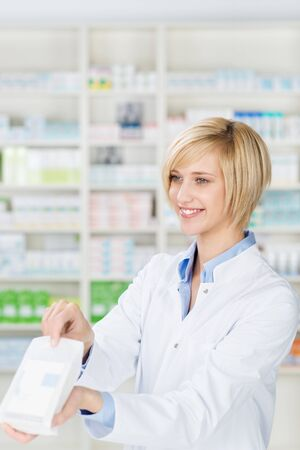 Happy young female pharmacist giving prescription medicines in pharmacy photo
