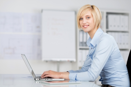 Side view portrait of young businesswoman using laptop at desk in office photo
