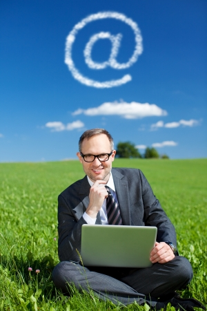grassfield: Conceptual portrait of businessman browsing the internet in grassfield Stock Photo