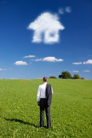 Man droomt van een nieuw huis staat met zijn rug naar de camera en zijn pak jas hing over zijn schouder naar buiten over een groen gebied met een wolk in de vorm van een huis in de blauwe hemel