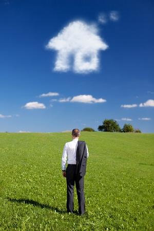 Man droomt van een nieuw huis staat met zijn rug naar de camera en zijn pak jas hing over zijn schouder naar buiten over een groen gebied met een wolk in de vorm van een huis in de blauwe hemel Stockfoto