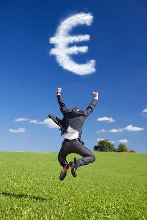greenfield: Conceptual portrait of businessman jumping in Greenfield with Euro Sign from the Clouds Stock Photo