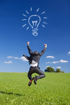 Conceptual portrait of businessman jumping in Greenfield with Bulb from clouds