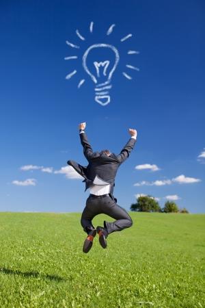 Conceptuele portret van zakenman springen in Greenfield met Bol van wolken