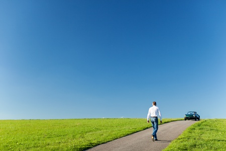recedes: Man walking along a tarred road running through a green field towards his cabriolet car parked on the horizon against a sunny blue sky Stock Photo