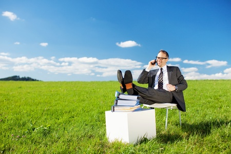Business concept shot of businessman calling with his feet up on his books in a green field with a bright blue sky photo