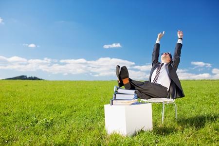 éxtasis: Hombre de negocios levantando los brazos con los pies en la pila de libros en Greenfield