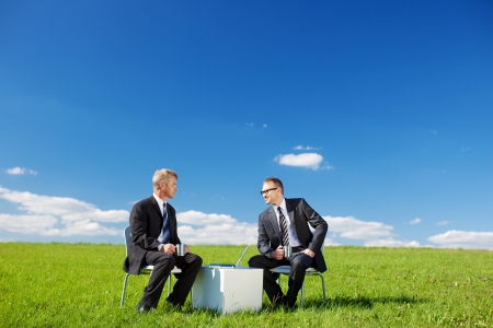 greenfield: Two businessmen sitting and talking with laptop in Greenfield Stock Photo