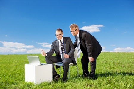 Two businessmen having a meeting with laptop in green meadow photo