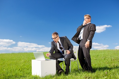 Conceptual shot of surprised businessmen with laptop in green meadow photo