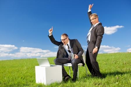 exultant: Happy businessmen raising their hands in front of laptop in green meadow