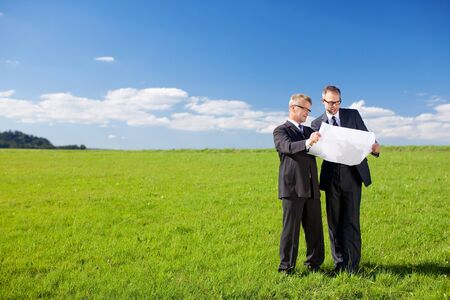 building planners: Conceptual portrait of two businessmen holding a construction plan in green meadow