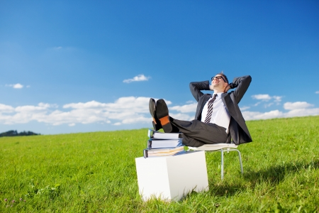 Businessman resting with his feet laying on stack of books in green meadow photo