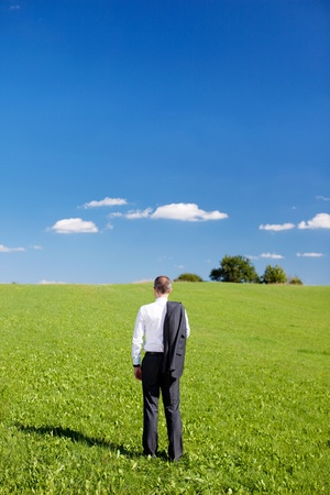 Businessman in a green field standing with his back to the camera and jacket slung over his shoulder looking out over the countryside photo