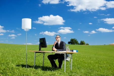 Smiling businessman working with computer and table in green meadow