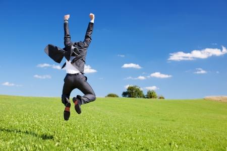 Zakenman springen van vreugde vieren van een succesvolle prestatie in een weelderige groene veld onder een blauwe hemel