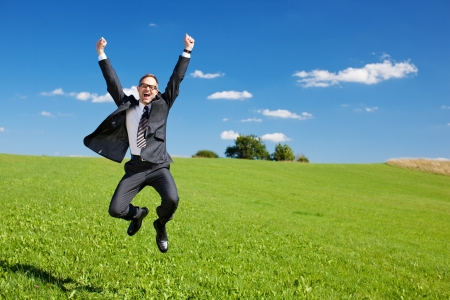 jubilation: Excited businessman jumps high in the air cheering and celebrating a success or achievement in a green sunny field under a blue sky Stock Photo