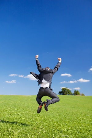 jump suit: Jubilant businessman jumping for joy with his arms raised and back to the camera in a lush green field Stock Photo