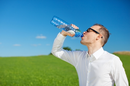 Man drinking bottled water gulping it down to quench his thirst standing sideways in a green sunny field photo