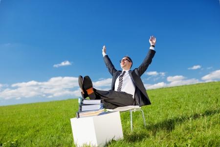 Empresario de relax al aire libre sentado en una silla en un campo verde, con los pies encima de una pila de documentos y los brazos levantados hacia el sol Foto de archivo