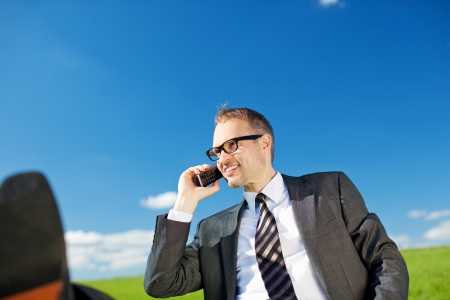 Low angle view of a handsome business man chatting on his mobile phone under a sunny blue sky photo